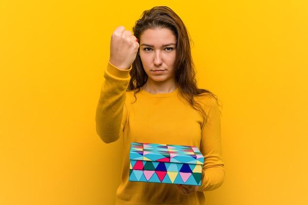 Jovem mulher europeia segurando um presente, mostrando o punho para a câmera, expressão facial agressiva.