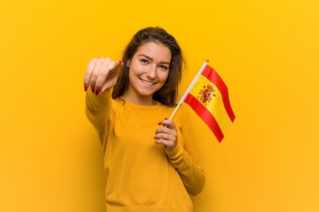 Jovem mulher europeia segurando um sorriso alegre bandeira espanhola apontando para a frente