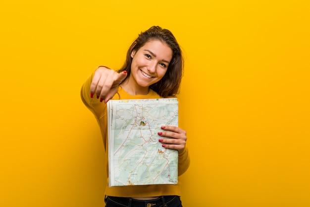 Jovem mulher europeia segurando um sorriso alegre de mapa apontando para a frente.
