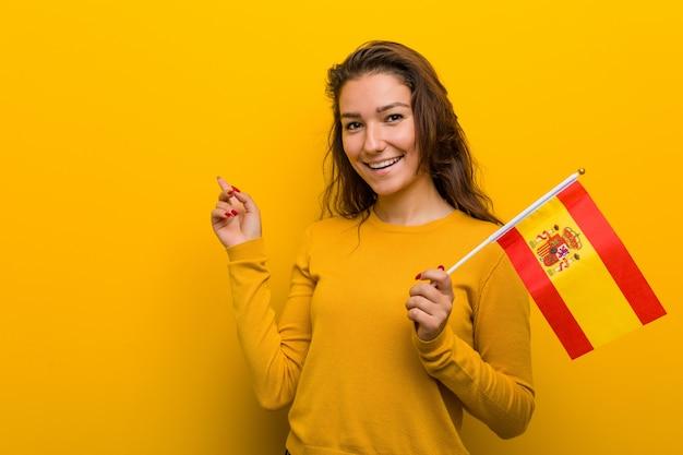 Jovem mulher europeia segurando uma bandeira espanhola, sorrindo alegremente apontando com o dedo indicador.