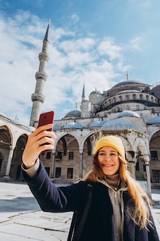 Jovem mulher europeia tira um retrato de selfie em istambul, turquia. garota atravessa o inverno de istambul. loira tira uma foto no telefone no contexto de uma mesquita em dia de outono.