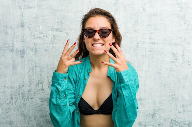 Jovem mulher europeia usando biquíni chateada, gritando com as mãos tensas.