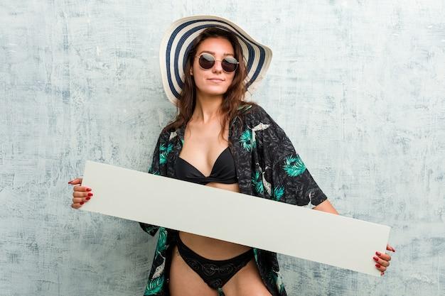 Jovem mulher europeia usando biquíni e segurando um cartaz