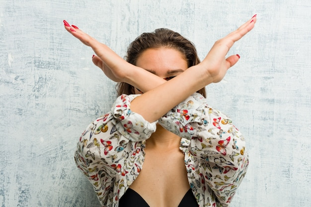 Jovem mulher europeia usando biquíni, mantendo os dois braços cruzados, conceito de negação.