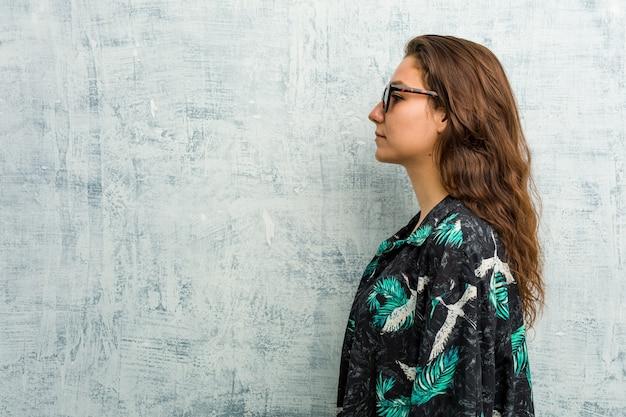 Jovem mulher europeia usando biquíni olhando para a esquerda, pose de lado.