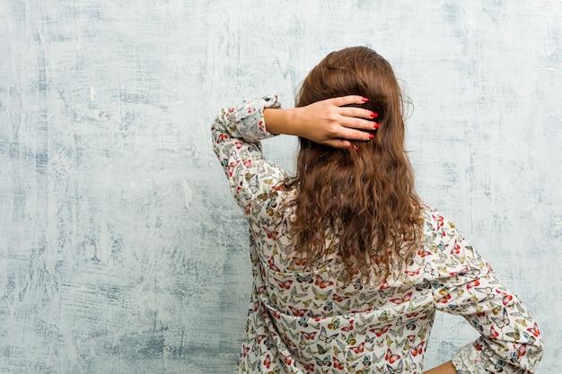 Jovem mulher europeia usando biquíni por trás, pensando em algo.