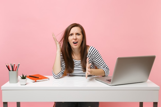 Jovem mulher exausta e irritada na perplexidade, espalhando as mãos, sente-se, trabalha na mesa branca com o laptop pc contemporâneo isolado no fundo rosa pastel. conceito de carreira empresarial de realização. copie o espaço.