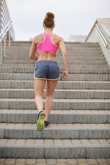 Jovem mulher exercitando ao ar livre. mulher atlética subindo as escadas correndo