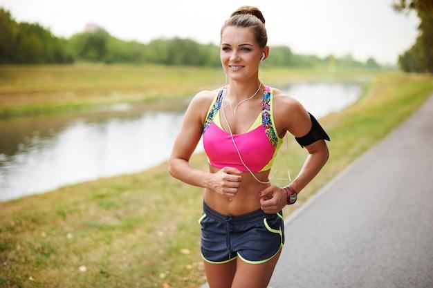 Jovem mulher exercitando ao ar livre. mulher correndo no ambiente natural