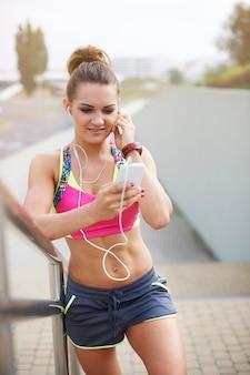 Jovem mulher exercitando ao ar livre. pausa curta para tocar minha música favorita