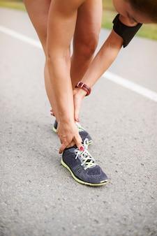 Jovem mulher exercitando ao ar livre. receio que meu tornozelo esteja torcido