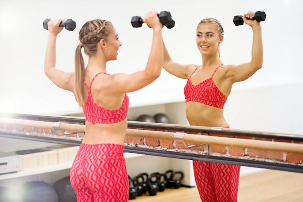 Jovem mulher exercitando com dumbells no ginásio
