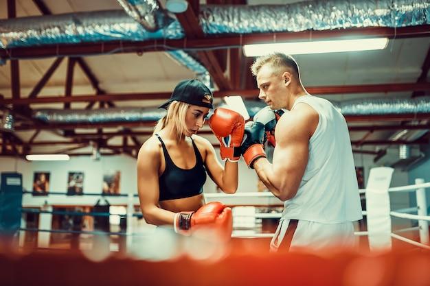 Jovem mulher exercitando com o treinador na aula de boxe e defesa pessoal