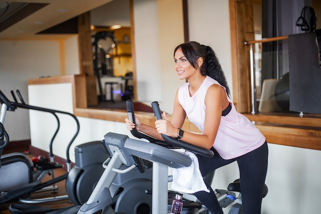 Jovem mulher exercitando com peso na academia