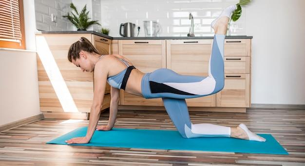 Jovem mulher exercitando em casa