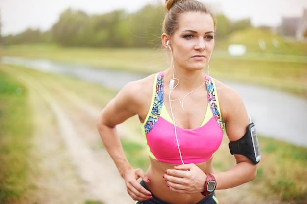 Jovem mulher exercitando fora. o mau tempo não é um problema para mim