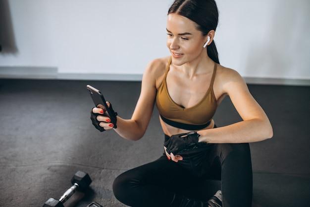 Jovem mulher exercitando na academia com halteres