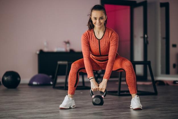 Jovem mulher exercitando na academia com peso
