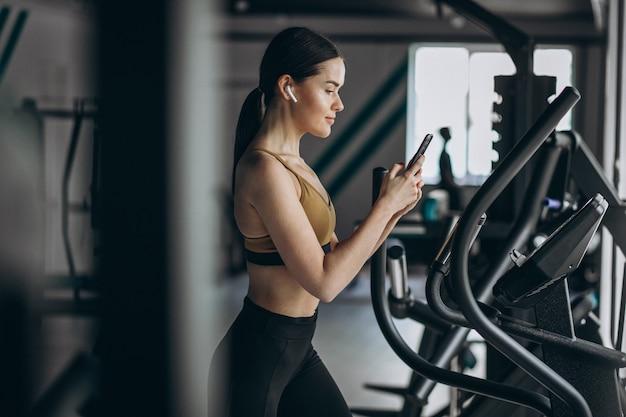 Jovem mulher exercitando na academia elíptica