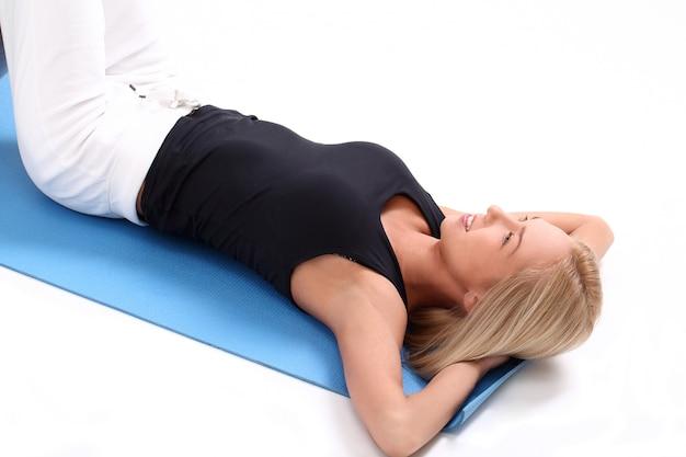 Jovem mulher exercitando na esteira da ioga