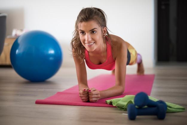 Jovem mulher exercitando-se em casa. finalmente, tenho uma motivação para fazer isso