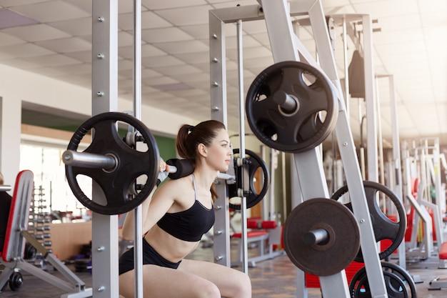 Jovem mulher exercitando usando barra com pesos pesados no health club. fêmea em roupas esportivas e com rabo de cavalo fazendo agachamentos no ginásio, o modelo de fitness ganha peso e desenvolve força.