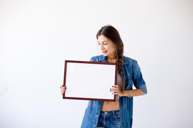 Jovem mulher exibindo um cartaz ou cartaz branco em branco