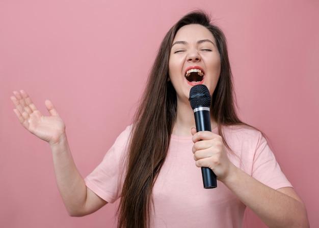 Jovem mulher expressiva com microfone na mão em fundo rosa