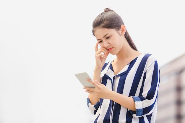 Jovem mulher exterior do estilo de vida que olha no smartphone. conceito de negócios