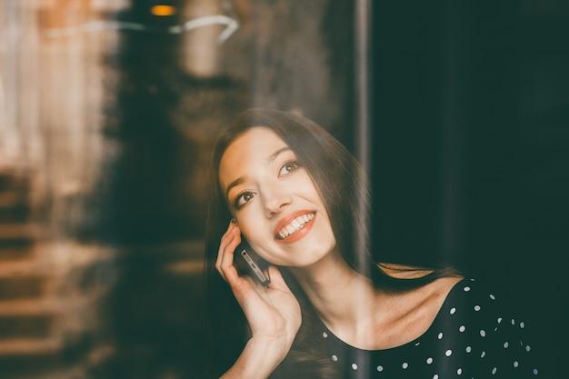 Jovem, mulher falando ao telefone com um grande sorriso