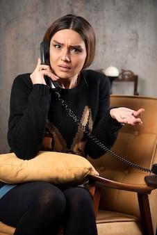 Jovem mulher falando ao telefone com uma expressão perplexa.