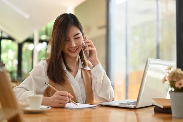 Jovem mulher falando ao telefone enquanto escreve no caderno no escritório.