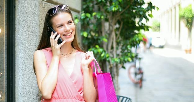 Jovem mulher falando ao telefone enquanto fazia compras em uma cidade