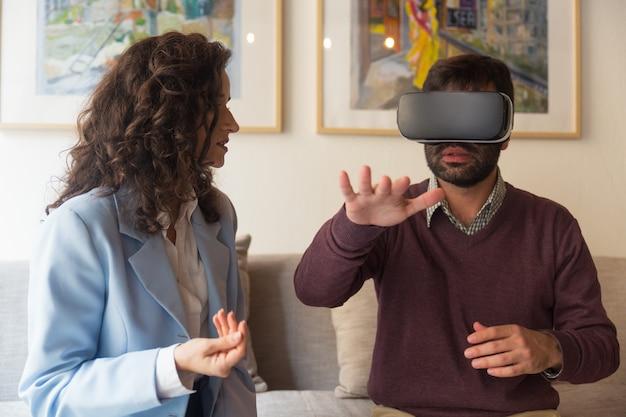 Jovem mulher falando com o homem de óculos vr tocando o ar
