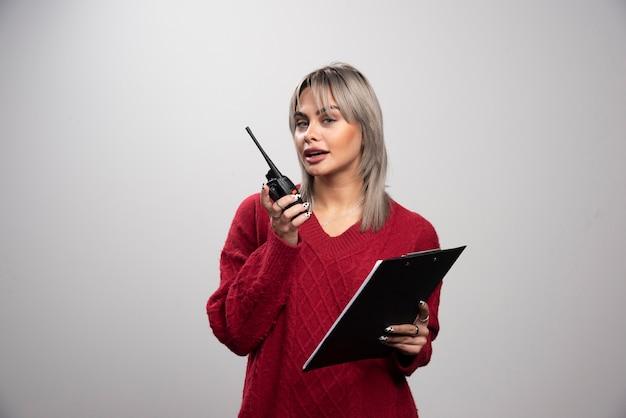 Jovem mulher falando com o transceptor de rádio e olhando para a câmera.