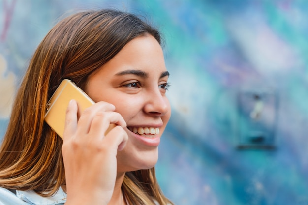Jovem mulher falando em seu telefone móvel.