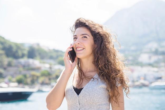 Jovem mulher falando no celular a sorrir