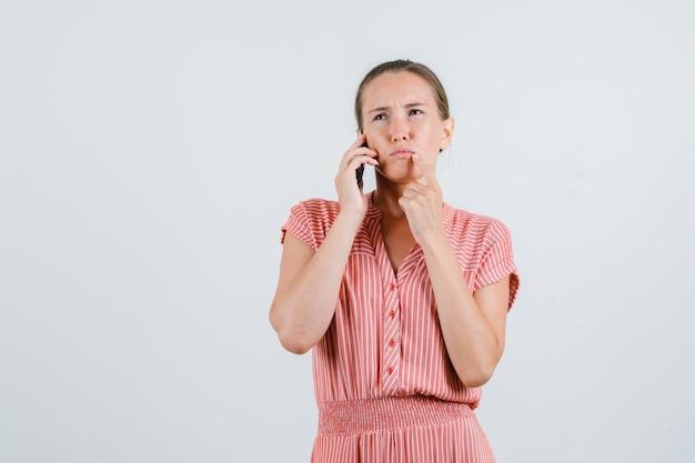 Jovem mulher falando no celular com vestido listrado e olhando pensativa, vista frontal.