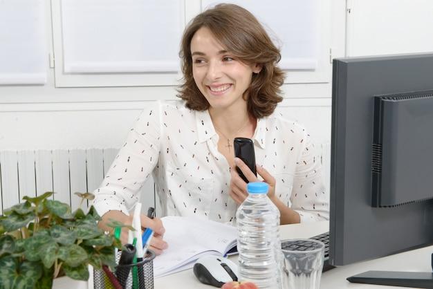 Jovem mulher falando no telefone e preenchendo o documento
