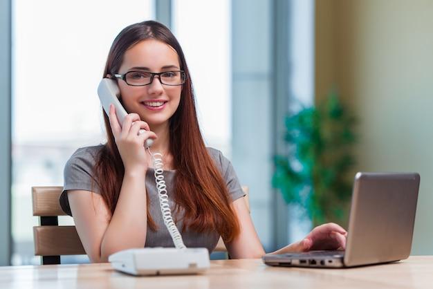 Jovem mulher falando no telefone no escritório