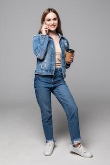 Jovem mulher falando pelo telefone móvel, bebendo café posando isolado sobre parede cinza
