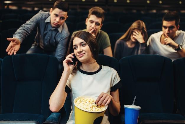Jovem mulher falando por telefone no cinema, público insatisfeito. showtime, filme assistindo