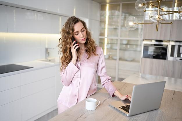 Jovem mulher falando smartphone e trabalhando em um laptop enquanto bebe café da manhã.