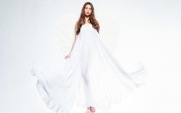 Jovem mulher fantasiada de anjo. anjo com presente. branco caído