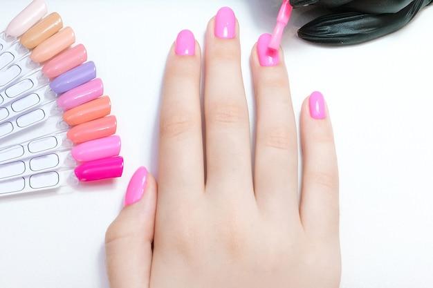 Jovem mulher faz as unhas no salão. aplicar goma-laca nas unhas. cor rosa