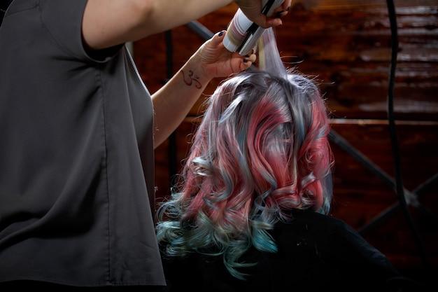Jovem mulher fazendo a coloração de cabelo e penteado no salão.