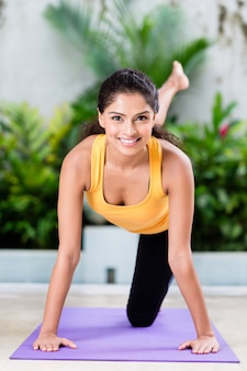 Jovem mulher fazendo alongamento exercício dentro de casa