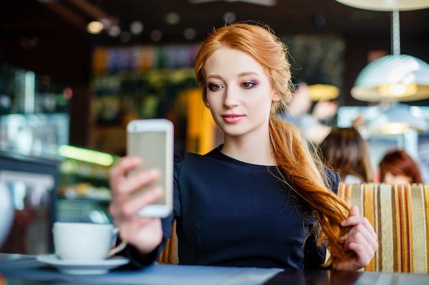 Jovem mulher fazendo auto-retrato usando smartphone