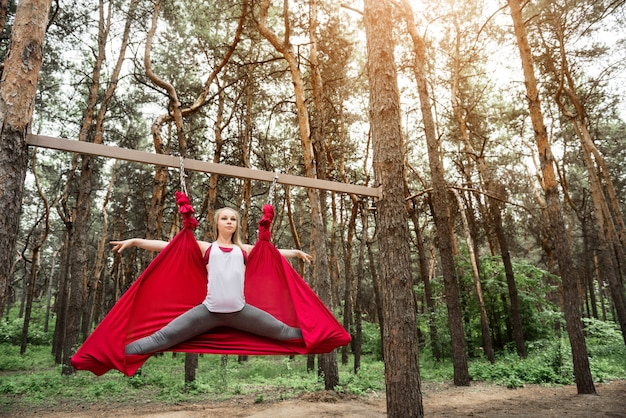 Jovem mulher fazendo barbante em uma rede para yoga