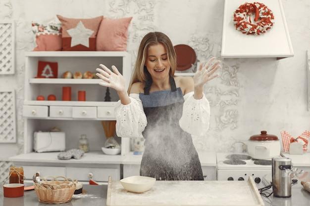 Jovem mulher fazendo biscoitos em forma de natal. sala de estar decorada com enfeites de natal ao fundo. mulher de avental.